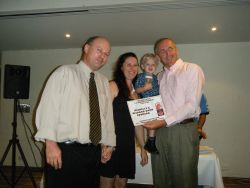 The owners receiving their award from the CEO of Dexter Laundry.